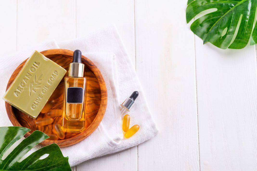 Sabonete, pílulas e óleo orgânicos de beleza em uma mesa branca. Ao lado folhas verdes compõem a imagem.