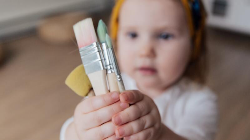 Criança, de aproximadamente quatro anos, desfocada. Em primeiro plano, suas mãos segurando quatro pincéis de pintar.