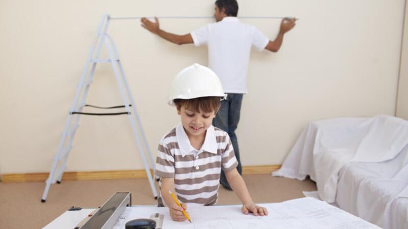 Criança brincando com planta baixa, enquanto o pai faz reparo na parede ao fundo.