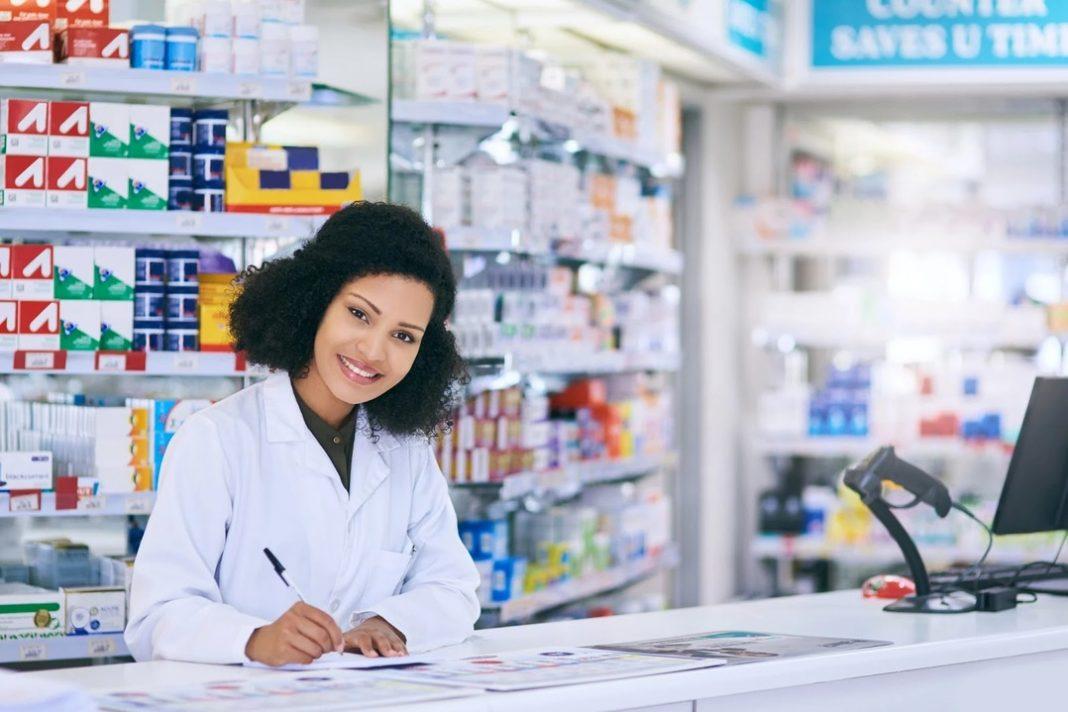 Mulher de jaleco branco sorrindo apoiada sobre balcão de farmácia segurando caneta sobre papel.