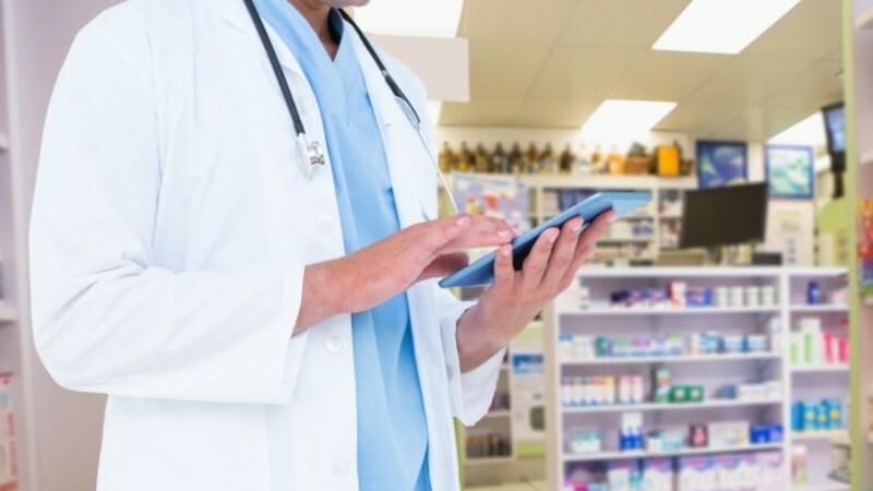 Farmacêutico segurando um tablet dentro da farmácia.