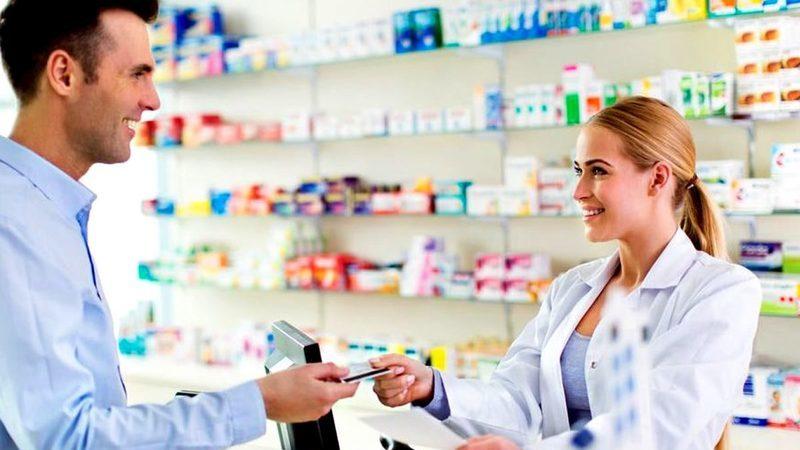 Homem de camisa social sorrindo e entregando cartão de crédito para mulher de jaleco no balcão da farmácia.