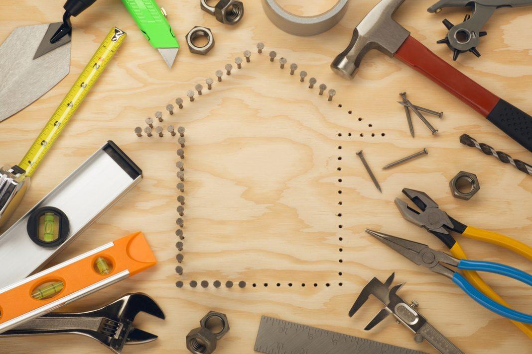 Contorno de casa incompleto feito de pregos sobre superfície de madeira. Ao lado, várias ferramentas espalhadas.