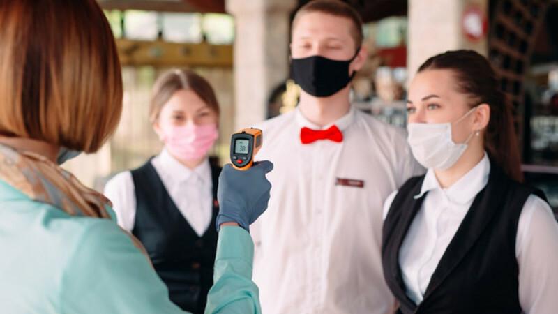 Gerente de hotel aferindo a temperatura de seus funcionários com termômetro à laser. Todos estão utilizando máscaras.