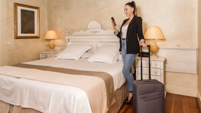 Hóspede contente fazendo o check-out em seu quarto usando smartphone.