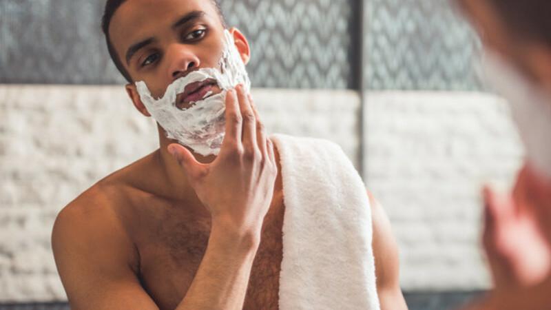 Homem concentrado fazendo a própria barba com espuma de barbear.