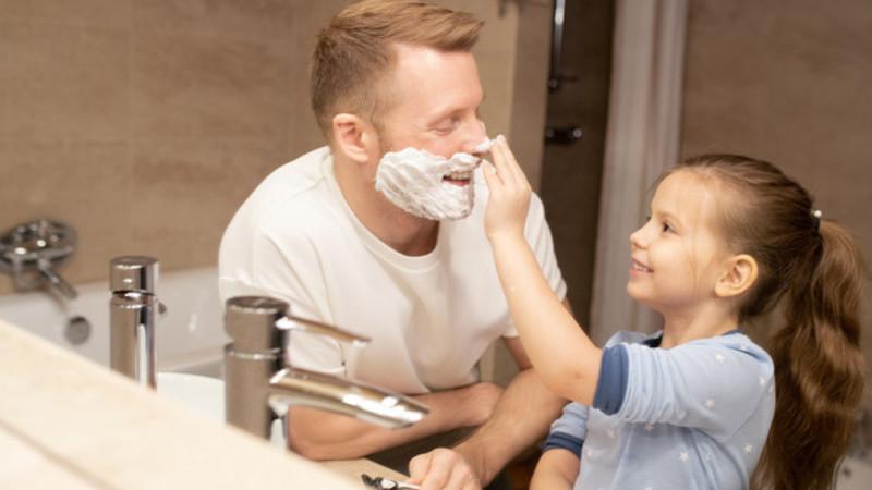 Criança passando espuma de barbear no nariz do pai que está com uma lâmina de barbear na mão.