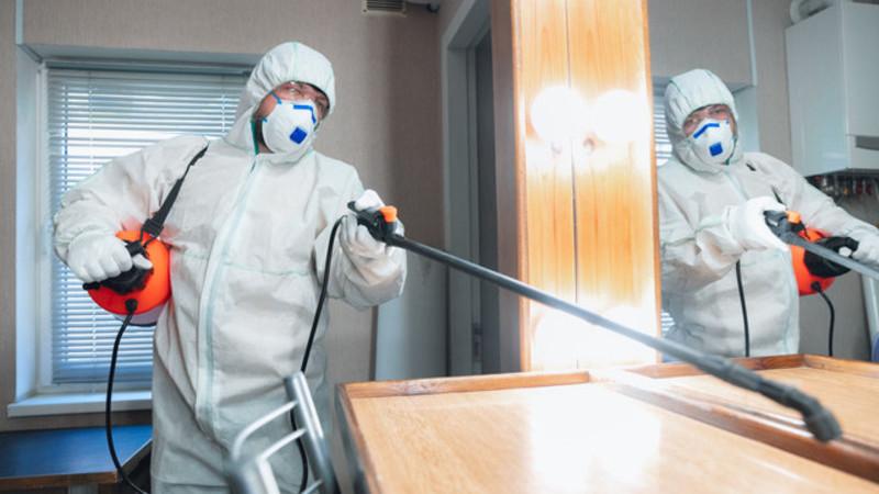Homem com o corpo todo coberto desinfetando um quarto de hotel com produtos de nível hospitalar.