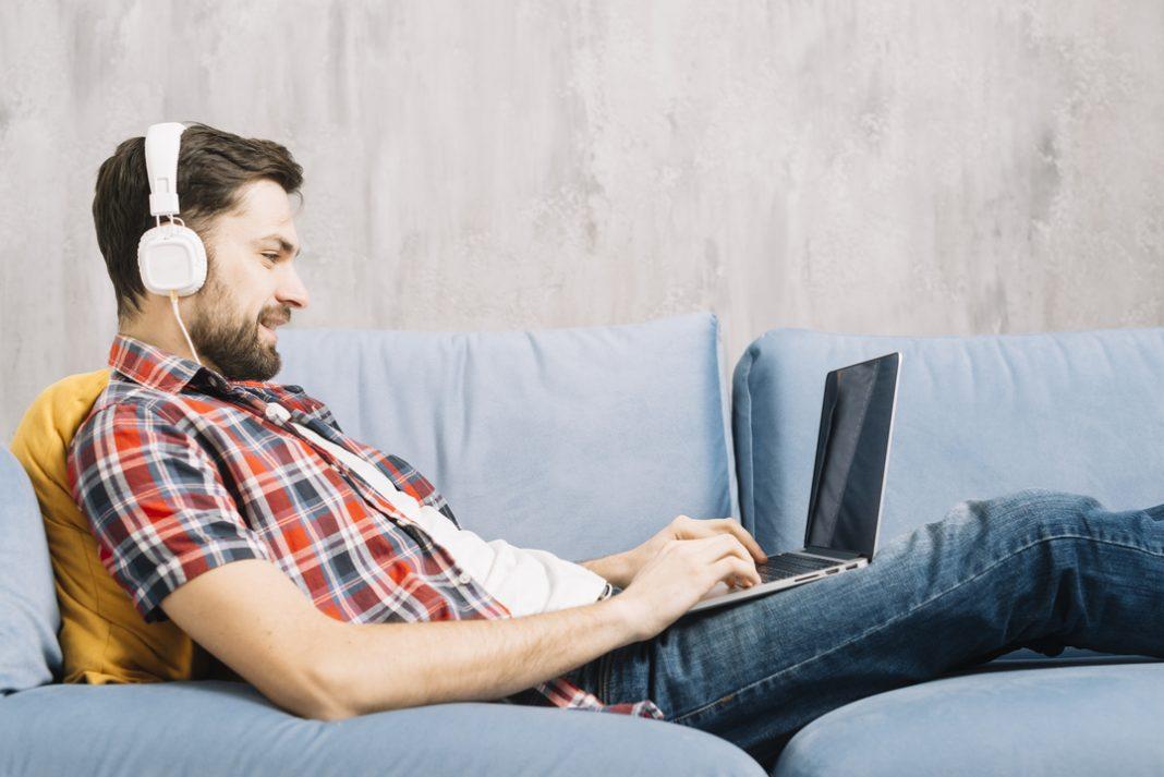 Homem com camisa xadrez deitado em um sofá azul, navegando pela internet pelo notebook com fones de ouvido.
