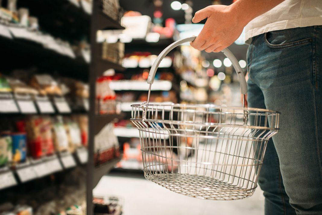 Homem parado em frente a prateleira de supermercado segurando cesta de compras de arame vazia.