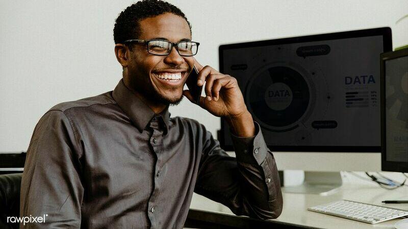 Homem de camisa social sentado em frente a um monitor sorrindo e segurando celular na orelha.