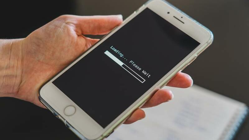 Uma mão segurando um smartphone com a tela loading. Ao fundo, desfocado um caderno.