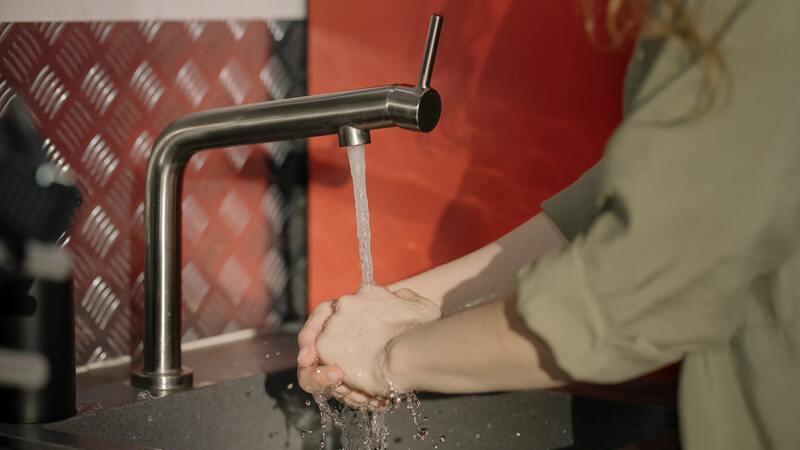 Mulher de blusa ¾ verde lavando as mãos em uma pia com parede de fundo vermelho ao fundo.