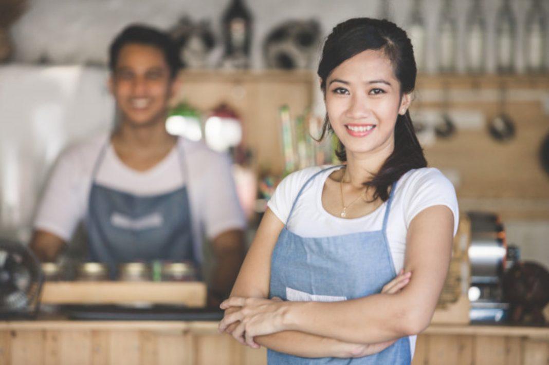 Mulher de braços cruzados na frente do balcão. Ao fundo homem cozinhando.