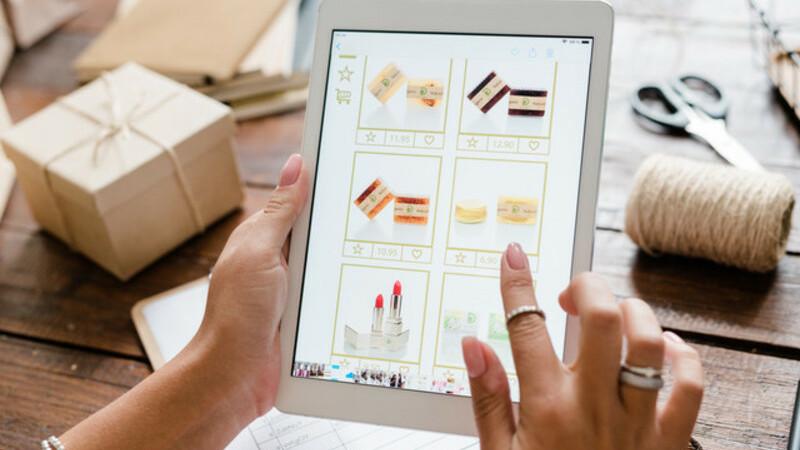 Mão de uma mulher comprando cosméticos pelo tablet