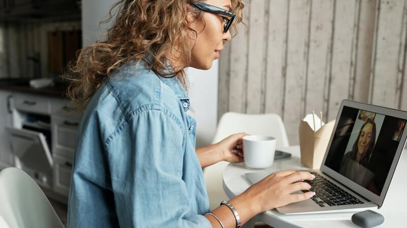 Mulher de óculos e blusa jeans sentada em uma cadeira branca. Ela faz uma vídeo chamada com outra mulher usando notebook.