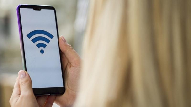 Mulher de costas com cabelo loiro olhando para a tela do celular com o símbolo de conexão ativa com a internet (wifi).