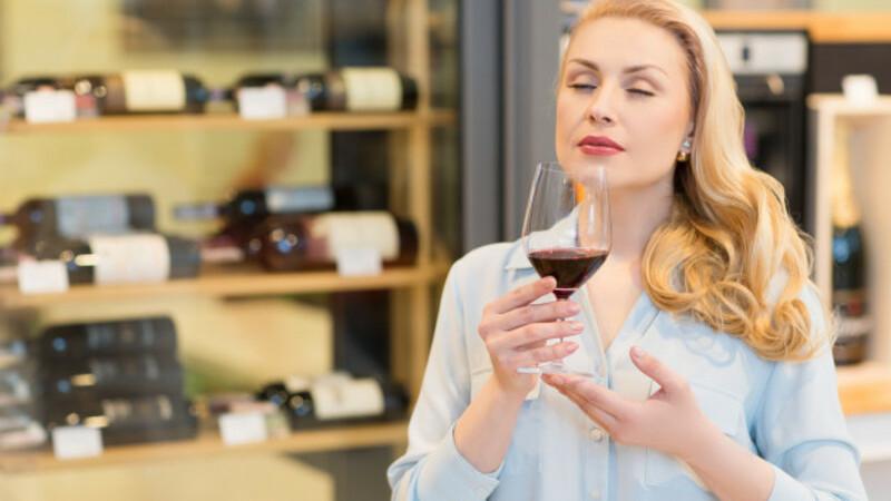 Mulher segurando e apreciando uma taça de vinho. Ao fundo, vários vinhos dispostos horizontalmente numa estante.