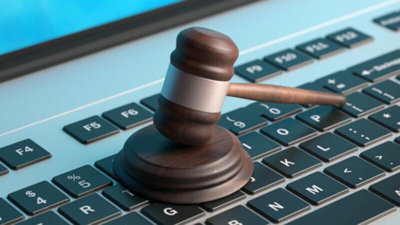 Malhete de juíz em cima de um teclado de laptop, simbolizando leis digitais