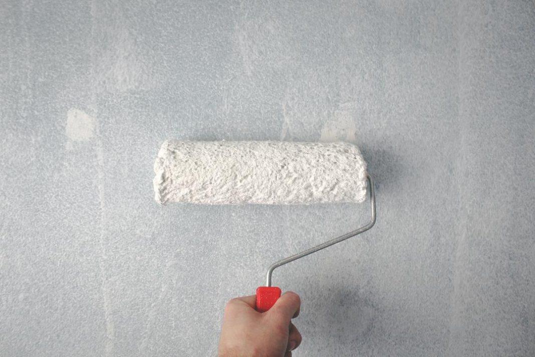 Mão segurando um pincel de parede de rolo com tinta branca e passando uma demão de tinta na parede também branca.