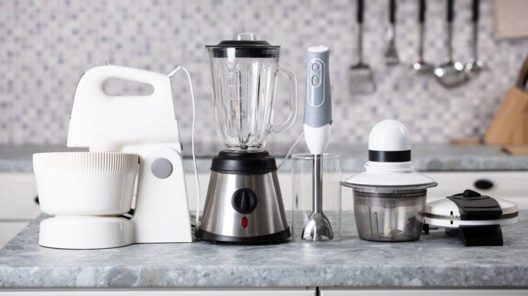 Batedeira branca, liquidificador prateado, mixer cinza, processador de alimentos e sanduicheira branca em bancada.