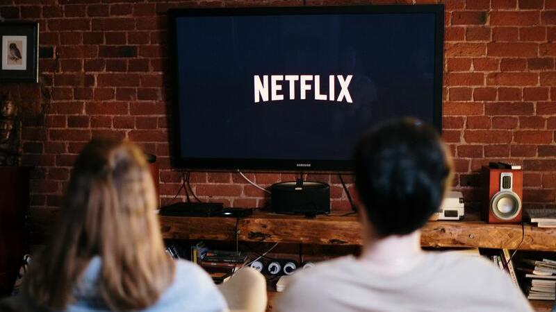 """Mulher e homem sentados de frente para uma Smart TV com """"Netflix"""" escrito na tela. Eles estão de costas para a câmera."""