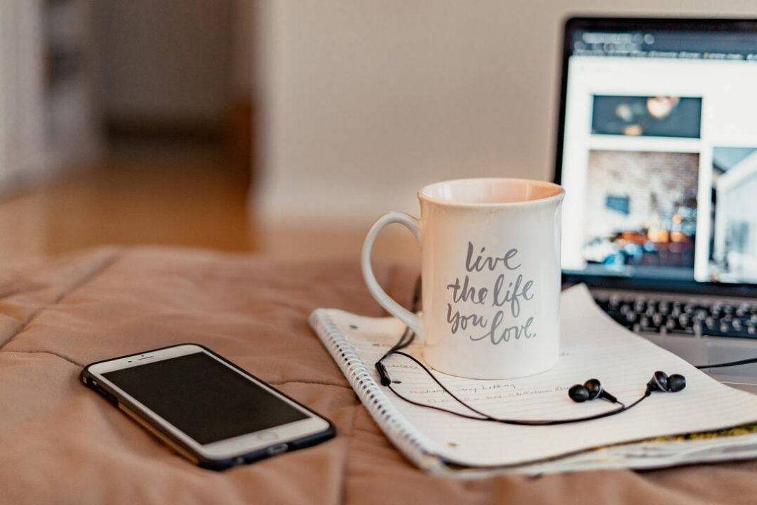 Smartphone, caderno, caneca, fones de ouvido e notebook aberto sobre superfície acolchoada.