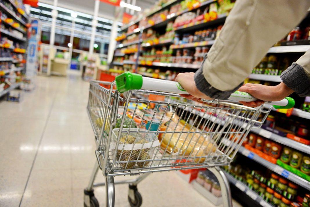 Braços de pessoa empurrando carrinho de compras em corredor de supermercado cercado de duas prateleiras de alimentos.