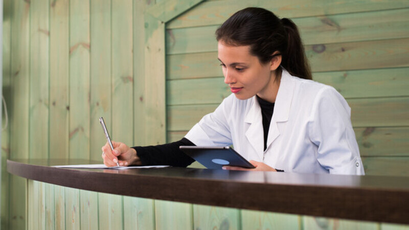 Jovem veterinária analisando tablet e fazendo anotações em um papel.