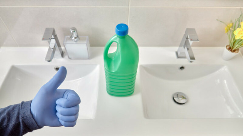 Embalagem verde, típica de água sanitária em cima de uma pia. Uma mão com luvas fazendo sinal de joinha.