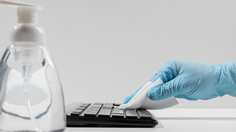 Embalagem transparente de álcool em gel em primeiro plano. Ao fundo uma mão limpando um teclado de computador.