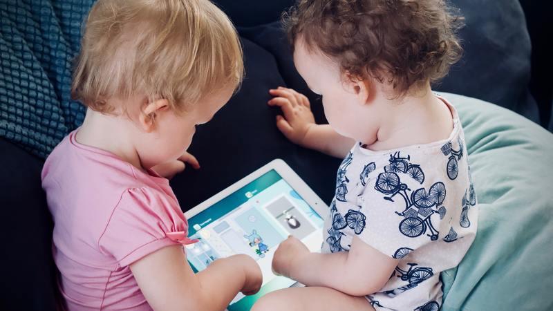 Dois bebês em um sofá segurando e teclando em um tablet. Ao lado há um travesseiro verde.