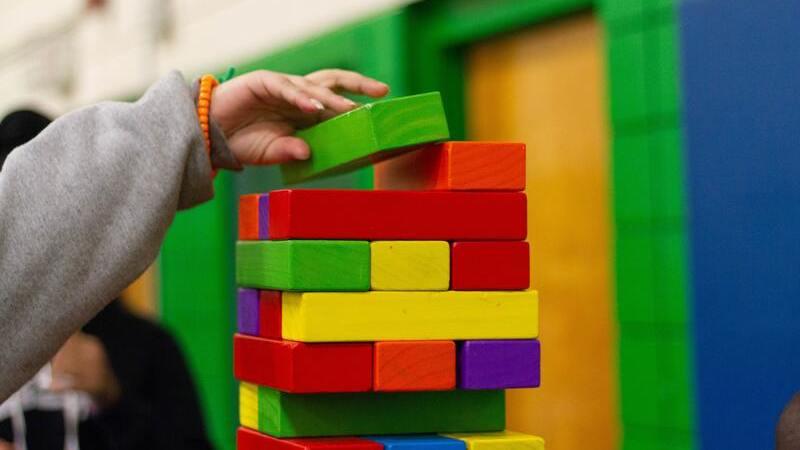 Mão de criança estendida sobre bloco colorido de montar. Ao fundo janela e paredes também coloridas