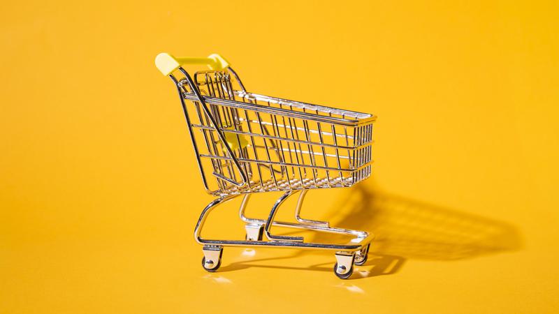 Imagem com um fundo laranja e um carrinho de compras metálico no centro.