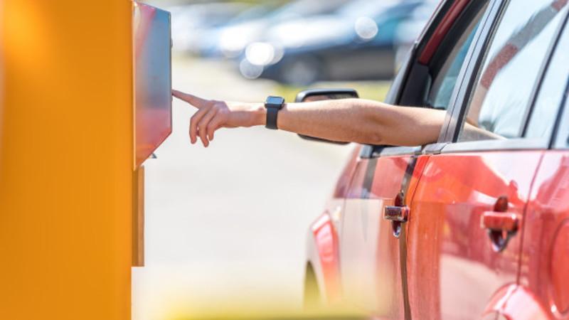 Cabine de pagamento de pedágio amarela e uma mão com relógio digitando os números saindo de um carro vermelho.