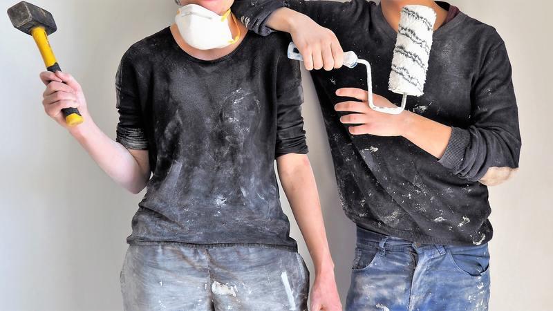 Casal usando máscara de proteção, segurando martelo e rolo de pintura. Suas roupas estão cheias de tinta.