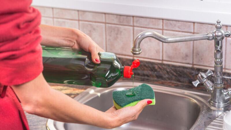 Mão feminina em frente a uma pia segurando e despejando detergente em uma bucha.