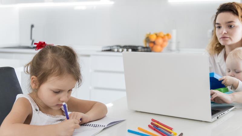 Imagem de uma mãe em home office trabalhando com um notebook e filho no colo. A sua frente filha desenhando.