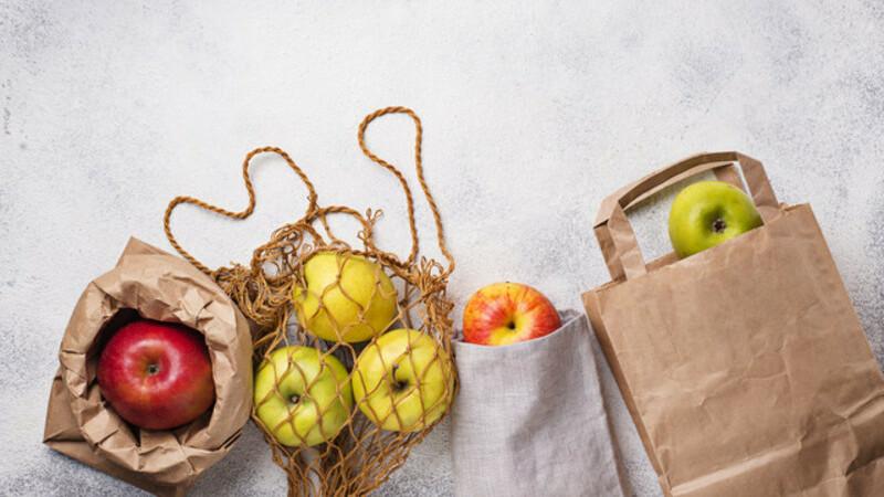Tipos diferentes de maçãs em tipos diferentes de sacolas: papel, tecido ecológico e fibra, formando uma espécie de rede