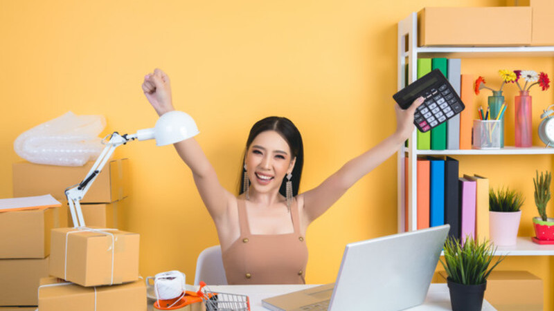 Empresária com braços levantados em comemoração, ela segura calculadora em uma das mãos. À sua frente, uma mesa com notebook