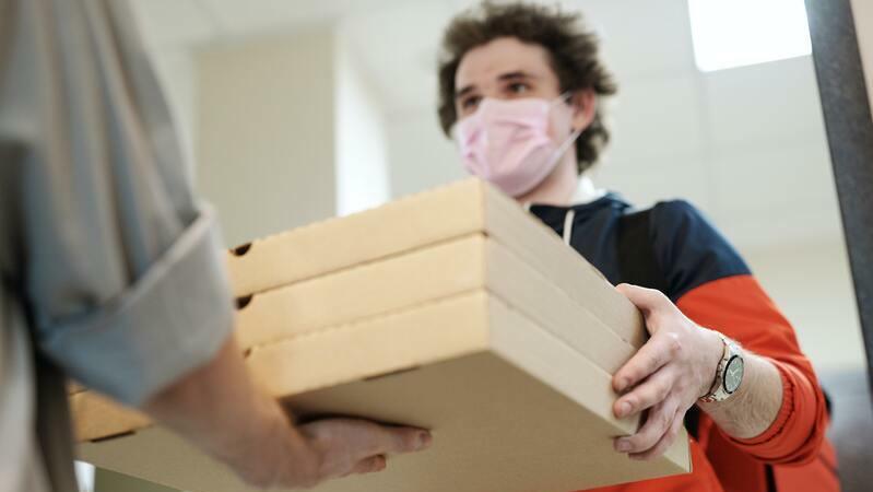 Entregador com moletom azul e vermelho, máscara de proteção rosa. Ele deixa três caixas de pizza nas mãos de outra pessoa.