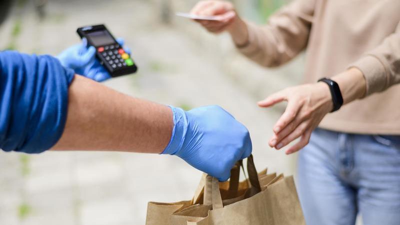 Motoboy com luvas azuis segura sacola de papelão em uma mão e a máquina de cartão em outra. Uma mulher recebe a encomenda.