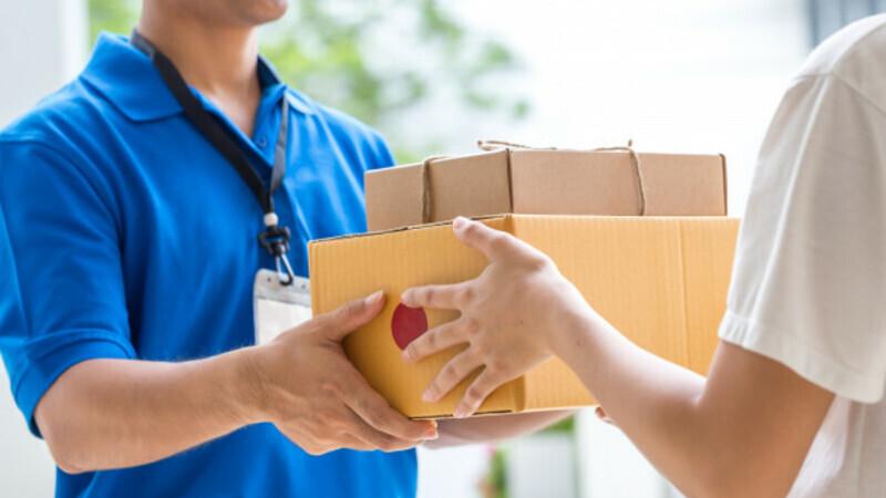Homem de camisa azul e crachá de identificação entregando duas caixas de papelão para uma pessoa.