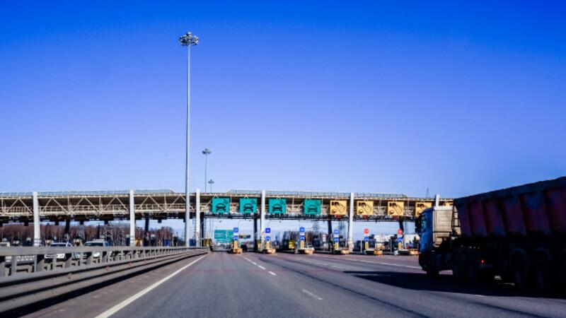 Foto de uma estrada com pedágio, com céu azul ao fundo e um caminhão no lado direito da foto, indo em direção à cancela.