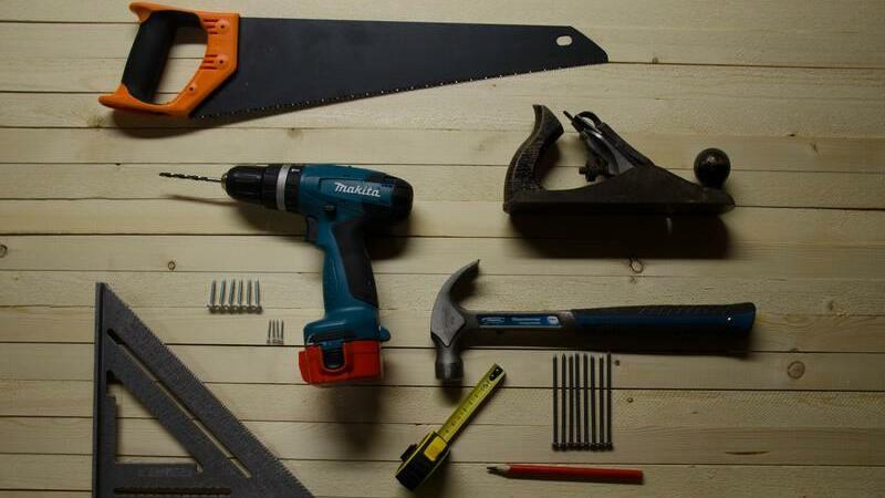 Serra, esquadro, furadeira, trena, martelo, pregos, lápis sobre superfície de madeira