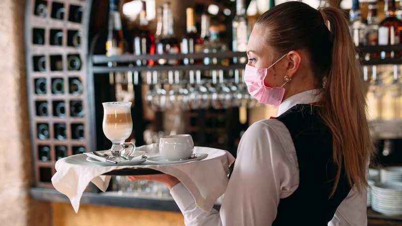 Mulher usando máscara facial cor de rosa, camisa branca e colete preto segurando bandeja com copo de café e louça branca.