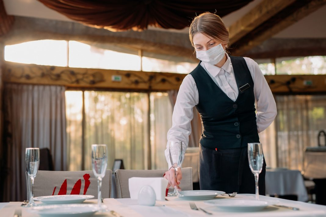 Garçonete usando máscara com uniforme preto e branco. Ela arruma taças em mesa.