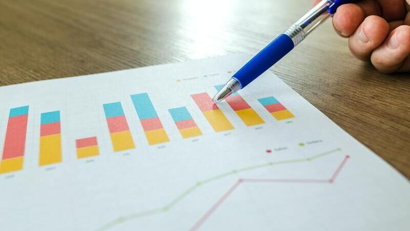 Sob uma mesa de madeira marrom, uma mão segura caneta da cor azul, apontando para um papel com gráficos coloridos.