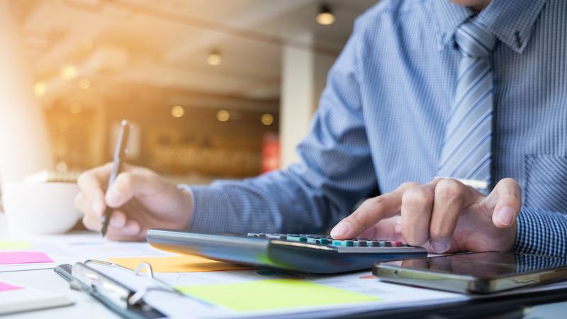 Foto de um empreendedor de camisa listrada azul e gravata listrada azul fazendo cálculos e anotando.