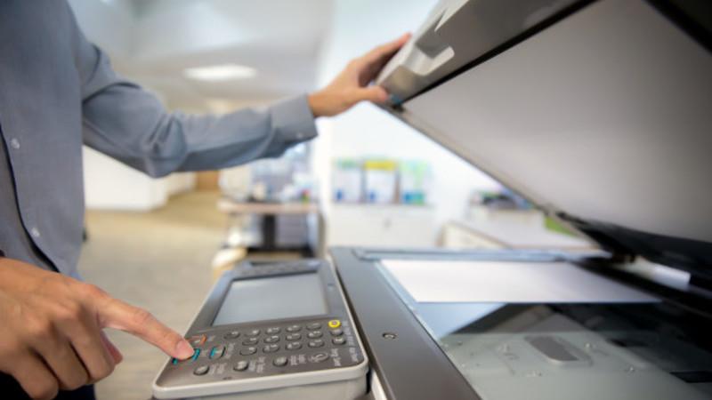 Homem com camisa social em uma empresa. Ele está teclando os botões de uma impressora.